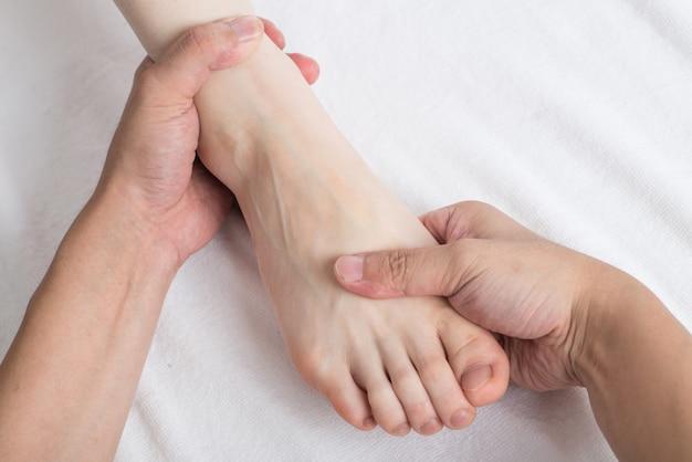 Close-up de mãos femininas, fazendo massagem nos pés