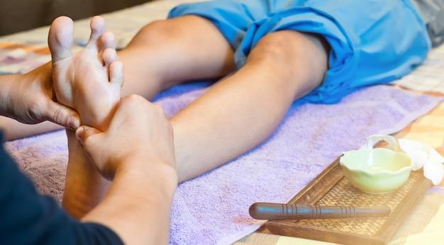 Close-up de mãos femininas, fazendo massagem nos pés.