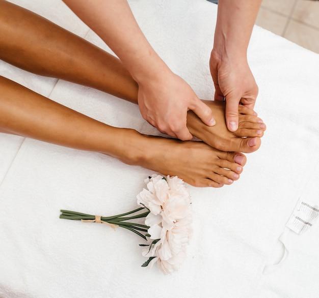 Close-up de mãos femininas fazendo massagem nos pés