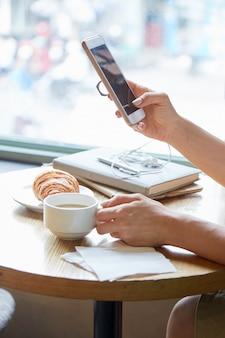 Close-up de mãos femininas irreconhecíveis, segurando o telefone e a xícara de café