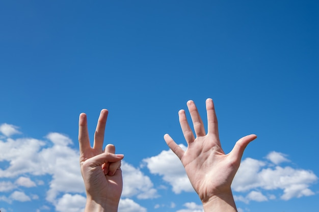 Close-up de mãos femininas, mostrando sete dedos em um céu azul.
