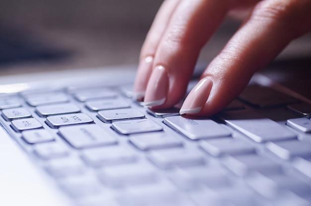 Close-up de mãos femininas no teclado do laptop