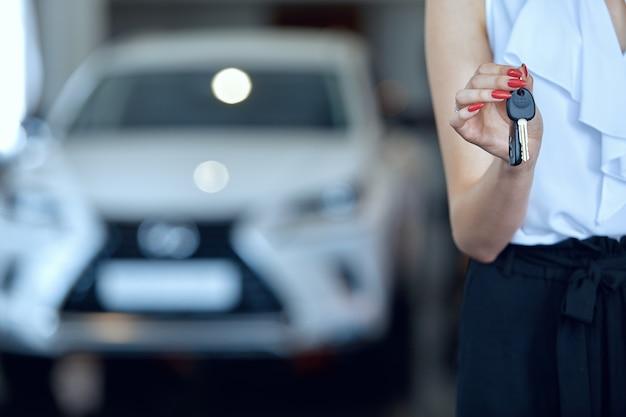 Close-up de mãos femininas segurando as chaves do carro.