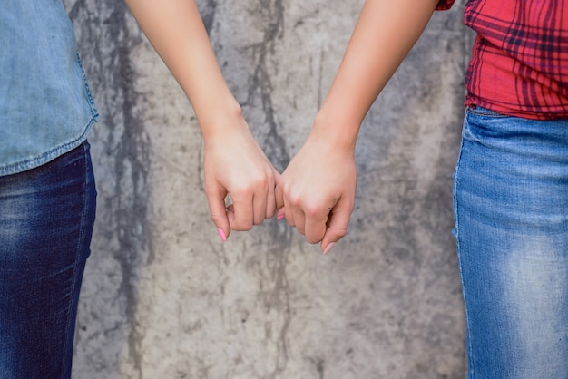 Close-up de mãos femininas segurando dedinhos isolados de parede cinza