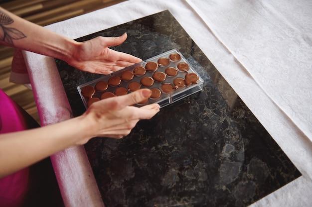 Close-up de mãos femininas segurando moldes de chocolate cheios de massa de chocolate aquecido líquido. preparando chocolates para comemorar o dia mundial do chocolate