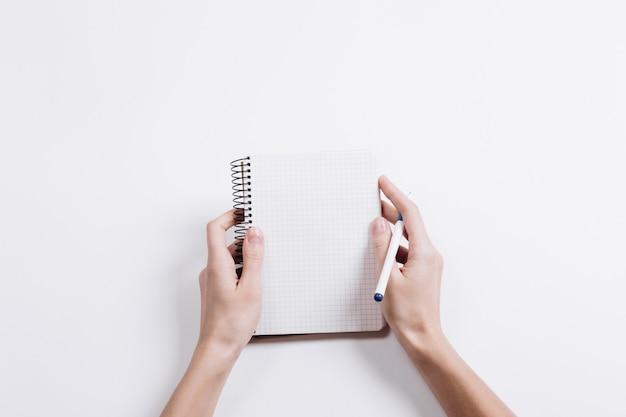 Close-up de mãos femininas segurando um bloco de notas em branco aberto e caneta