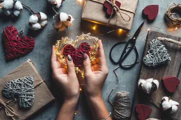 Close-up de mãos femininas segurando um presente em um coração rosa presentes para o dia dos namorados