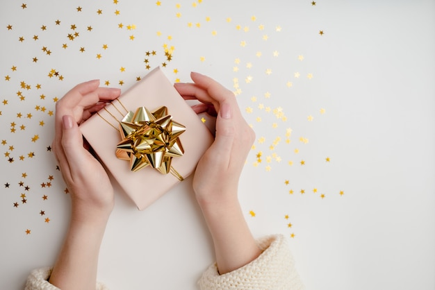 Close-up de mãos femininas segurando um presente. fundo festivo de natal com copyspace. vista horizontal superior