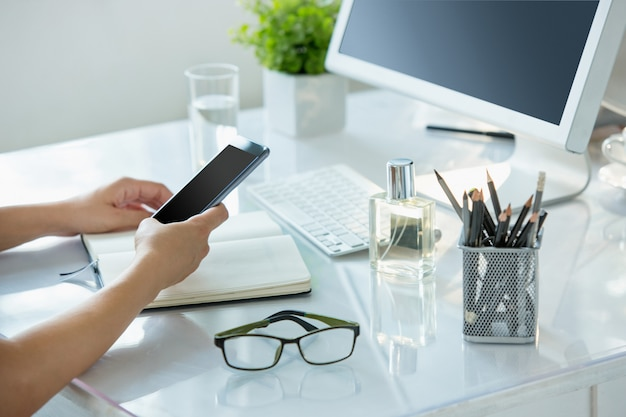 Close-up de mãos femininas, usando telefone inteligente enquanto trabalhava no computador no interior do escritório moderno