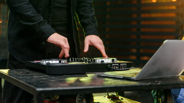 Close-up de mãos girando os decks na boate