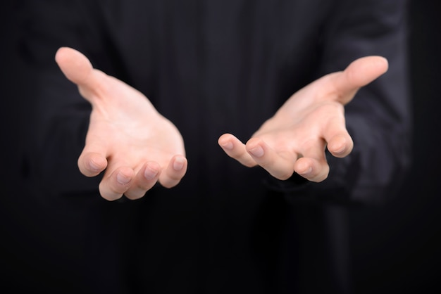 Close-up de mãos humanas, estendendo-se do escuro