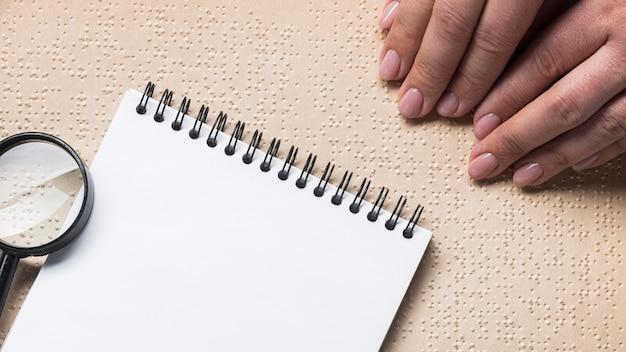 Close-up de mãos lendo livro em braille