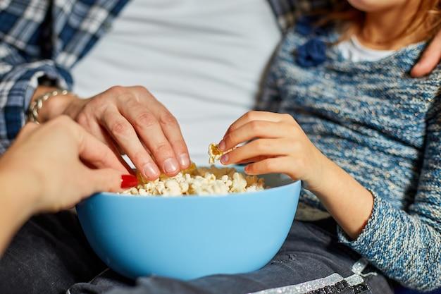 Close up de mãos mãe, pai e filha comem pipoca assistindo a um filme no sofá em casa