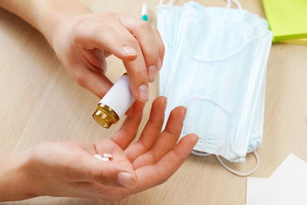 Close-up de mãos masculinas, derramando as pílulas do frasco de medicamento em um escritório