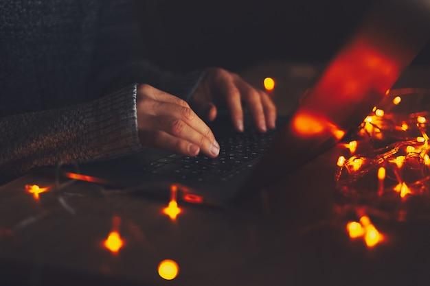 Close-up de mãos masculinas digitando no teclado do laptop em um quarto escuro com guirlandas.
