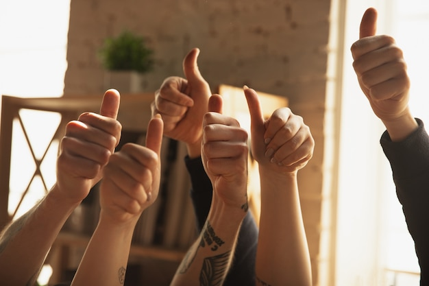 Close-up de mãos masculinas e femininas caucasianas mostrando bom, polegares para cima