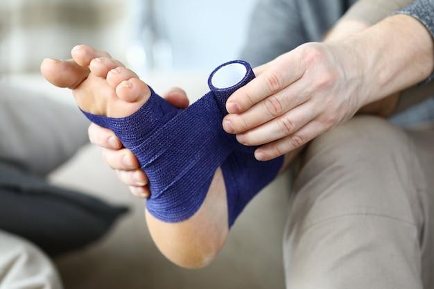 Close-up de mãos masculinas segurando a perna ferida. homem sentado no sofá com osso de fratura ou entorse.