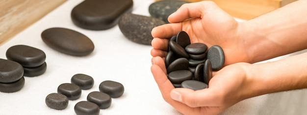 Close-up de mãos masculinas segurando pedras pretas do spa em suas palmas, sobre uma mesa branca no salão spa