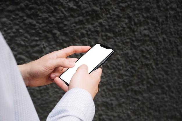 Close-up de mãos masculinas usando smartphone com tela em branco