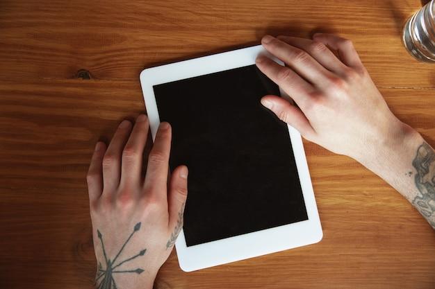 Close-up de mãos masculinas usando tablet com tela em branco