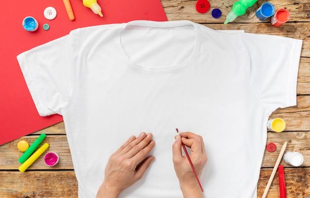 Close-up de mãos pintando camisa