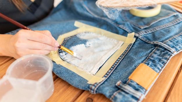 Close-up de mãos pintando jeans