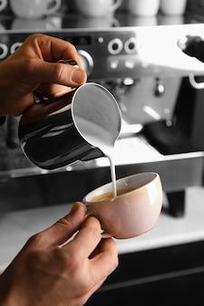 Close-up de mãos preparando café com leite
