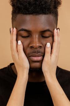 Close-up de mãos segurando o rosto de um homem