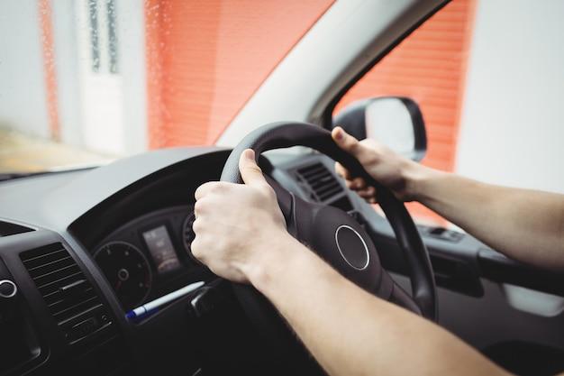 Close-up de mãos segurando o volante de uma van