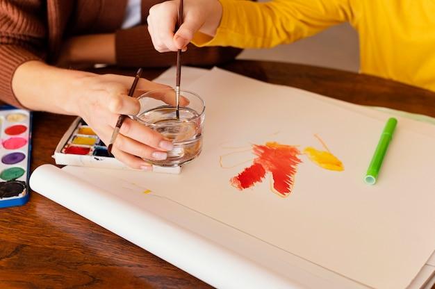 Close-up de mãos segurando pincéis de pintura
