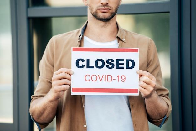 Close-up de mãos segurando um cartaz de covid19