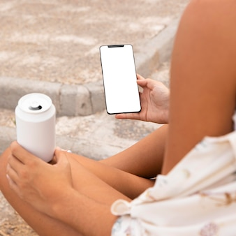 Close-up de mãos segurando um telefone e bebendo