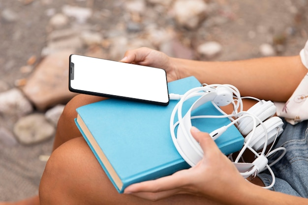 Close-up de mãos segurando um telefone e fones de ouvido