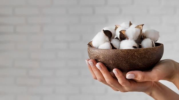 Close-up de mãos segurando uma tigela com algodão