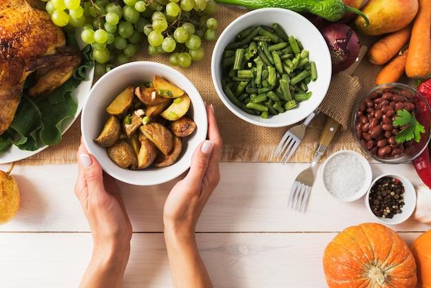 Close-up de mãos segurando uma tigela de batatas