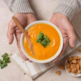 Close-up de mãos segurando uma tigela de sopa de creme