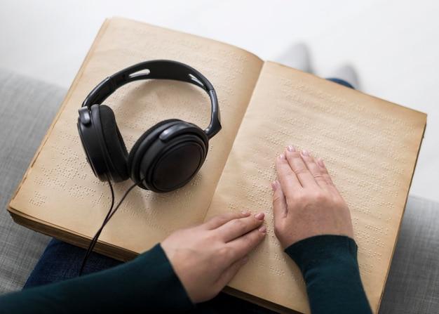 Close-up de mãos tocando livro em braille