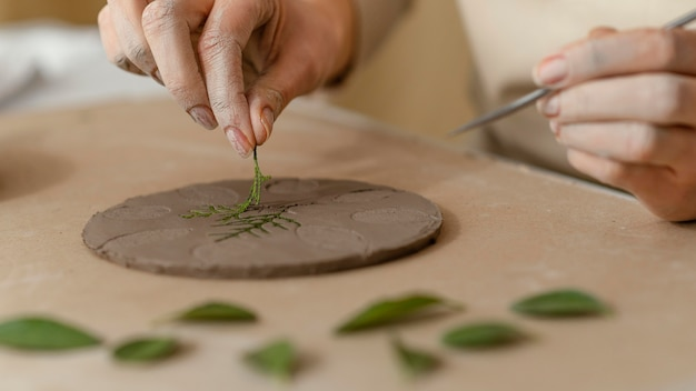 Close-up de mãos trabalhando com planta e argila