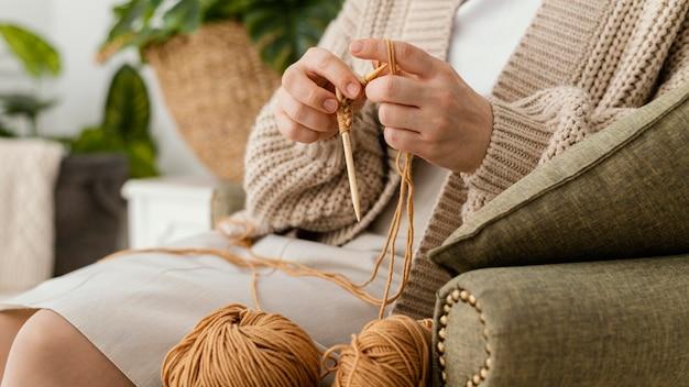 Close-up de mãos tricotando com agulhas