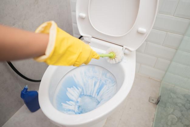 Close-up de mãos usando luvas e usando uma escova ao limpar o banheiro no banheiro