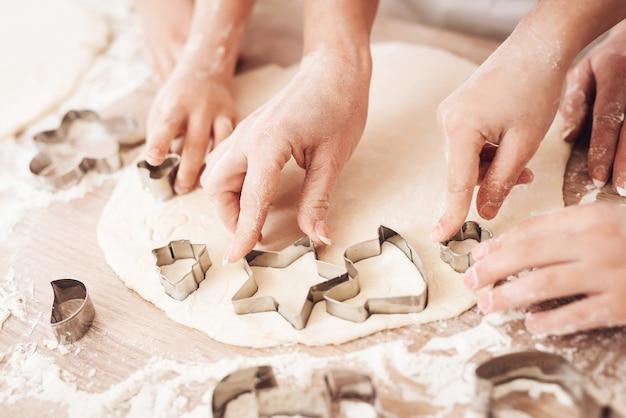 Close up de mãos usando o cortador de biscoitos na mesa