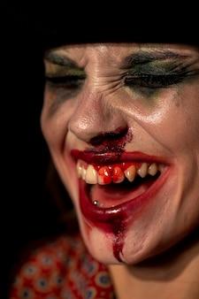 Close-up de maquiagem palhaço com sangue nos dentes