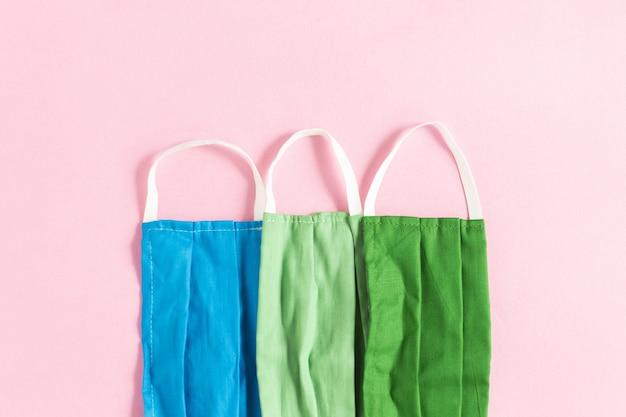 Close up de máscaras protetoras azuis, verdes claras e verdes escuras em um fundo rosa