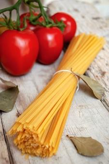 Close-up de massa espaguete cru ao lado de tomates vermelhos frescos em um galho e folhas de louro em uma superfície de madeira.