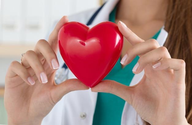 Close-up de médico feminino mãos segurando ler coração. cuidados de saúde, cardiologia e conceito médico
