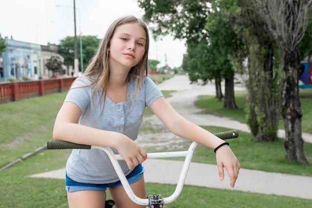 Close-up, de, menina adolescente, sentando, ligado, bicicleta, parque