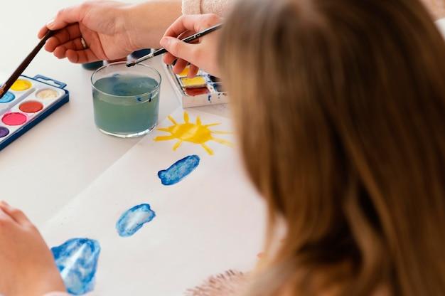 Close-up de menina pintando com aquarela