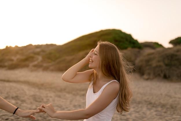 Close-up, de, menina sorridente, segurando, dela, amigo, mão, em, praia