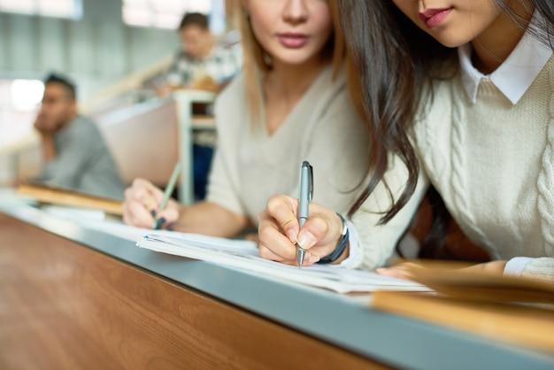 Close-up de meninas tomando notas na aula