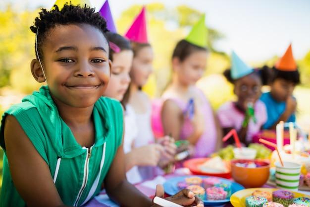 Close-up de menino bonitinho sorrindo na frente de outras crianças durante uma festa de aniversário